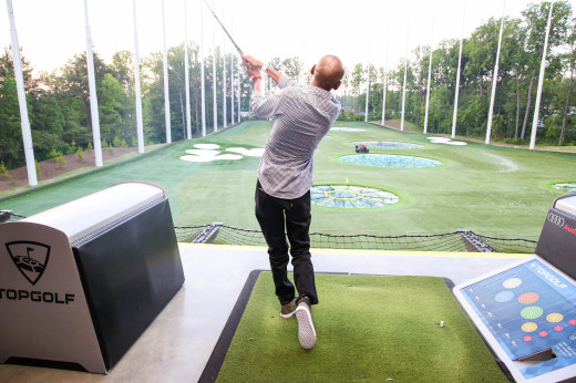 Host Robert Powell takes a swing during a round of golf